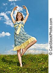 Young girl dancing in meadow