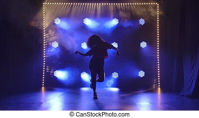 Young girl dancing jazz funk in the studio in slow motion. Silhouette against the background of blue lights