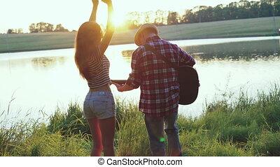 Young girl dancing when boy playing guitar near the lake. 4k