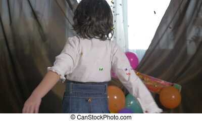 Young girl dancing with confetti