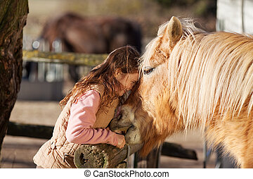 Young girl demonstrating affection for her horse outdoors in...