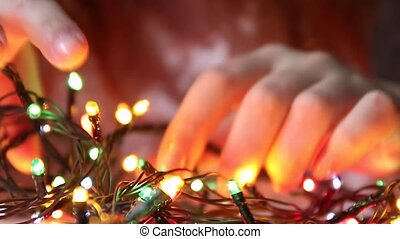 Young girl disassemble the Christmas luminous garland for ...