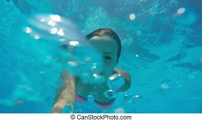 Young girl dives under water in the ocean