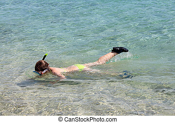 young girl diving in the sea on summer vacation