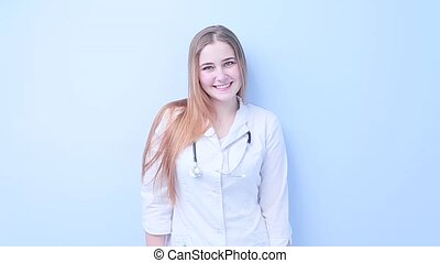Young girl doctor smiling on a light background