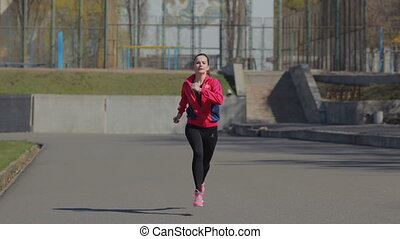 Young girl doing a race at the stadium. Starts running on...