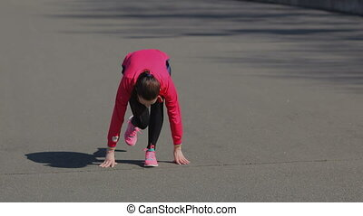Young girl doing a race at the stadium. Become a rack to...