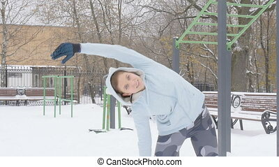 Young girl doing fitness exercise in the outdoors Winter