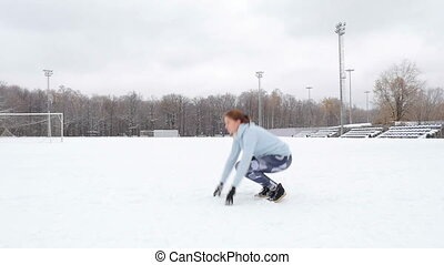 Young girl doing fitness exercises outdoors Winter