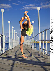 Young girl doing gymnastic exercises on the pier (normal ver)