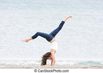 young girl doing gymnastics on sea background