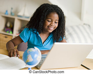 Young Girl Doing Her Homework On A Laptop