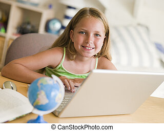 Young Girl Doing Homework On A Laptop
