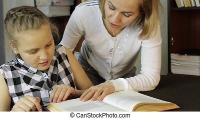 Young girl doing homework together with her mother. mom compels daughter to reads
