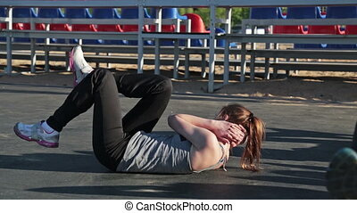 Young girl doing sit-ups exercising together