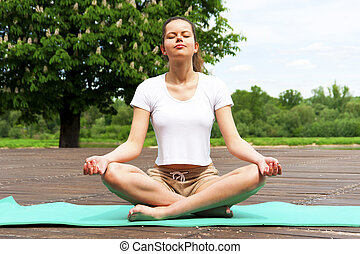 Young girl doing yoga in the park