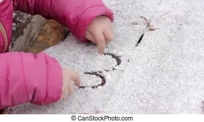 young girl draw on a snowy table, childrens games in a winter wood