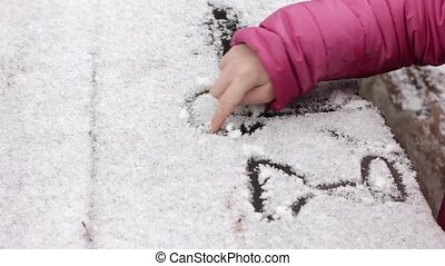 young girl draw on a snowy table, childrens games in a...