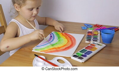 Young girl draws a colorful rainbow