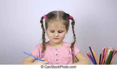 Young girl draws on a paper. Education concept