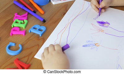Young girl draws with felt-tip pens - Young girl draws...