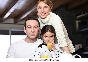 Young girl drinking a glass of orange juice while posing for the camera with her parents