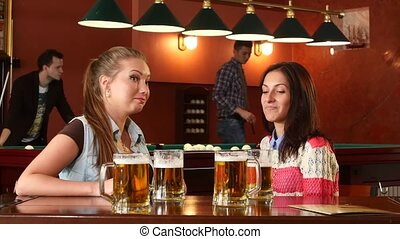 Young girl drinking beer at the bar on a background of billiards