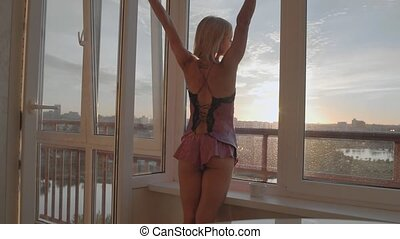 Young girl drinking coffee near the window at sunrise