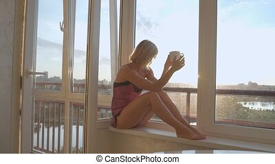 Young girl drinking coffee near the window at sunrise.