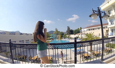 Young girl drinking cup of coffee on the hotel balcony during summer vacation. Woman thoughtfully looking out over hotel pool and drink beverage. Close up Slow motion