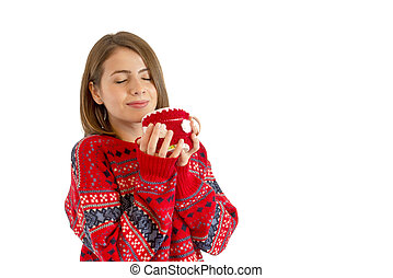 Young girl drinking from a mug in the winter season, isolated on white background