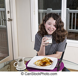 Young Girl Drinking Milk with her Breakfast Meal