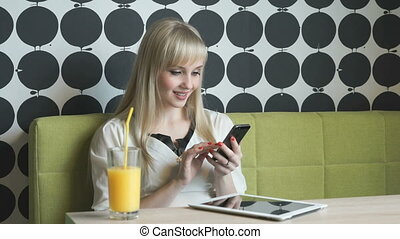 Young girl drinking orange juice at the cafe