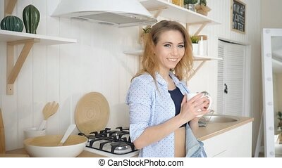 Young girl drinks coffee and smiling at kitchen, slow motion