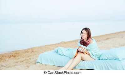 Young girl drinks coffee on the beach