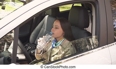 Young girl drinks cold waterin the car