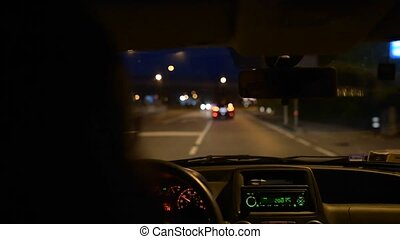 Young girl driving a car on city road night.