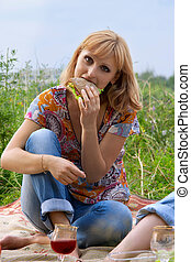 Young girl eating a sandwich at a picnic
