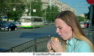 Young girl eating a stale tasteless hamburger. spits down