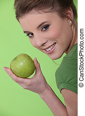 young girl eating apple against green background