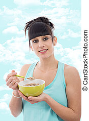 Young girl eating bowl of healthy breakfast cereal