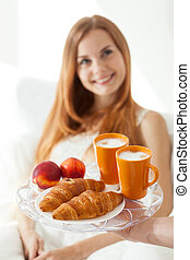 Young girl eating breakfast in bed