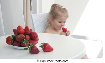 Young girl eating strawberries