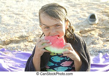 Young girl eats a slice of watermelon in summer on the beach, closeup portrait