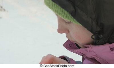 Young girl eats chips in the winter forest