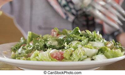 Young girl eats salat.