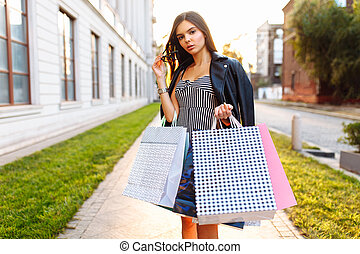 Young girl enjoying a successful shopping, on the background of a beautiful sunset, in nature, with bags in hand