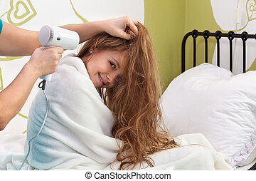 Young girl enjoying her hair being dried after bath