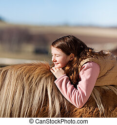 Young girl enjoying the sun laying on a horse back