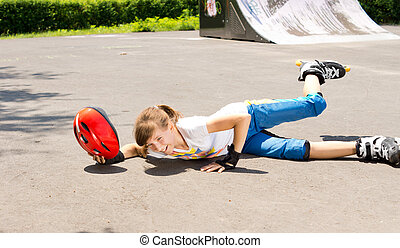 Young girl falling while roller skating lying sprawled on...